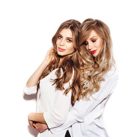 Twee mooie zusters vrouwen met gezond lang haar krullen dragen witte shirts. Meisjes knuffelen op witte achtergrond niet geïsoleerd