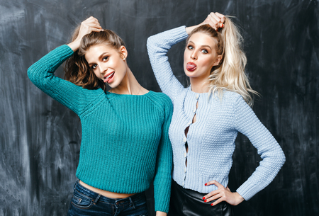 teenage girl: portrait of two pretty hipster sisters wearing colorful knit sweaters . Girls smile, have fun against black wall.