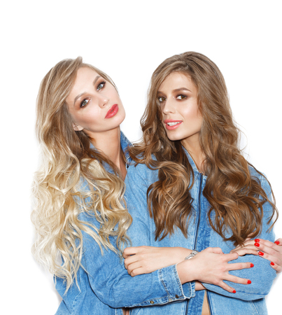 sisters sexy: Portrait of two pretty sisters girls wearing stylish jeans jackets. Young women over white background not isolated