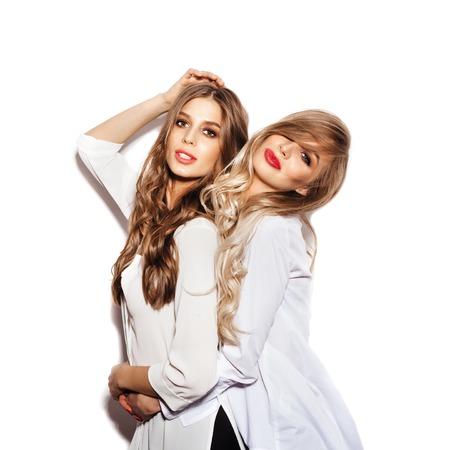 2 つのきれいな白いシャツを着て長い髪を健康なジャノメの姉妹女性。孤立していない白い背景に楽しんで女の子