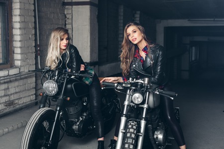ringlets: Sexy biker girls sitting on vintage custom motorcycles. Beautiful women with Healthy Long Hair ringlets wearing stylish leather jackets
