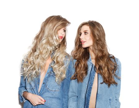 Close-up portret van twee mooie zussen dragen van stijlvolle jeans jassen. Meisjes lachen, plezier op witte achtergrond niet geïsoleerd Stockfoto