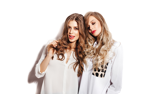 Two pretty sisters women with Healthy Long Hair ringlets wearing white shirts. Girls over white background not isolated