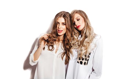 Twee mooie zusters vrouwen met gezond lang haar krullen dragen witte shirts. Meisjes op een witte achtergrond niet geïsoleerd