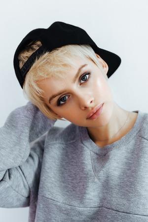 Hipster tiener meisje poseren over de muur. Street swag stijl, pet, natuurlijk kort haar, beauty model gezicht Stockfoto