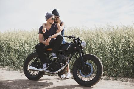 Jong romantisch koppel in een veld op een motorfiets. Liefde, vrijheid, samenhorigheidskoncept. Gelukkig man en meisje reizen op een motorfiets