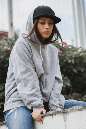 Young girl wearing blank and oversize long hoodie and black cap. Outdoors lifestyle portrait Zdjęcie Seryjne - 82651456