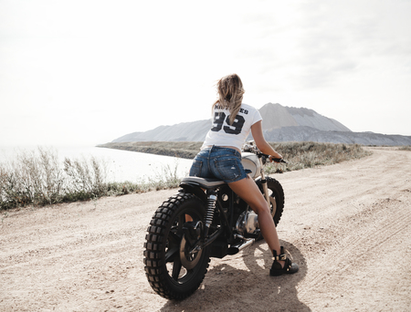 Young pretty cheerful woman sitting on custom cafe racer motorbike on the desert. Girl biker with perfect fit slim tamed body and long hairs. Outdoor lifestyle portrait
