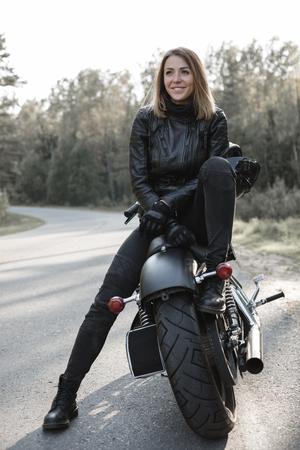 バイクの上に座って若いかなり陽気な女性。女の子バイカーにぴったりのスリムなボディと森でカスタム チョッパー バイクに適合します。アウトドア ・ ライフ スタイルの肖像画 写真素材 - 92366823