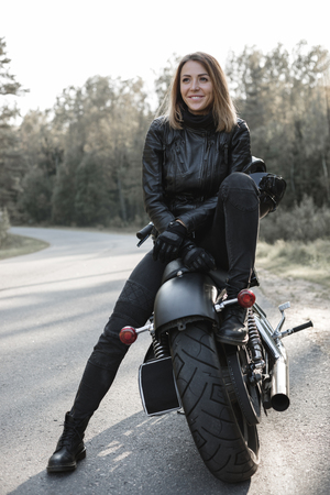 Young pretty cheerful woman sitting on motorcycle. Girl biker with perfect fit slim body and custom chopper motorbike at forest. Outdoor lifestyle portrait Stock Photo