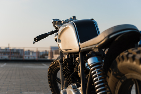 Close-up of custom motorcycle cafe racer on empty rooftop parking lot during sunset. Side view. Hipster lifestyle, student dream Stock Photo
