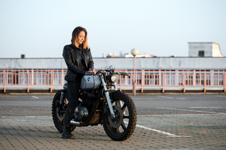 dorgeous woman biker chilling, relaxing on rooftop parking 스톡 콘텐츠