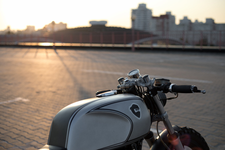 Close-up of motorcycle cafe racer on empty rooftop parking lot during sunset. Side view. Hipster lifestyle, student dream