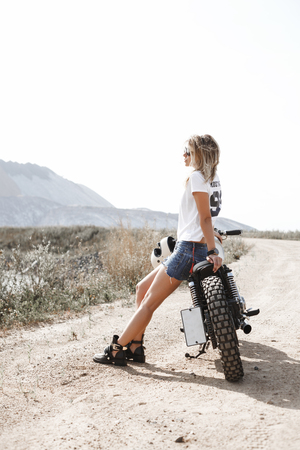 Sexy female rider holding helmet and sitting on her custom built cafe racer motorcycle in the desert Stock Photo