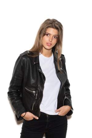 Girl biker in a black leather jacket having lowered hands in pockets Standard-Bild