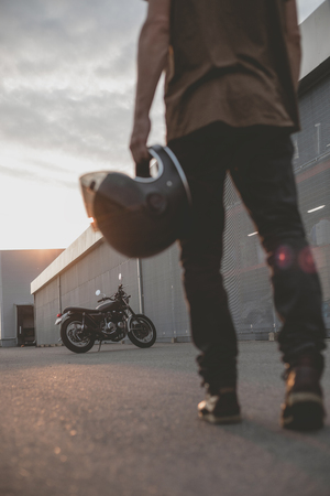 Close-up of a handsome rider biker guy hand with black helmet in front of classic style cafe racer motorcycle. Bike custom made in vintage garage. Brutal fun urban lifestyle. Outdoor portrait. Imagens