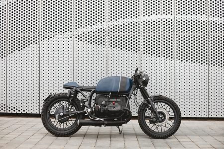 Black blue rebuilt vintage custom motorcycle cafe racer in front of wall