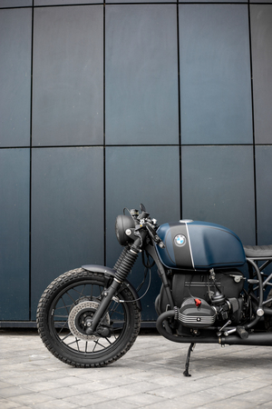 Black blue rebuilt vintage custom motorcycle cafe racer in front of wall