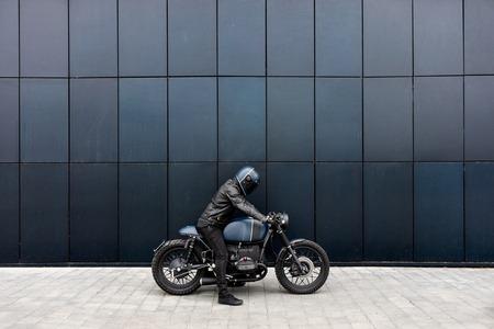 Biker man with Black blue rebuilt vintage custom motorcycle cafe racer in front of wall