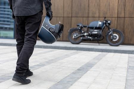 Zbliżenie: ręka faceta przystojny jeździec rowerzysta z czarnym kaskiem przed motocyklem cafe racer w stylu klasycznym. Rower wykonany na zamówienie w zabytkowym garażu. Brutalna zabawa w miejskim stylu życia. Portret plenerowy.