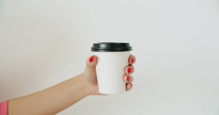 Mockup of female hand holding coffee paper cup on light white wall background