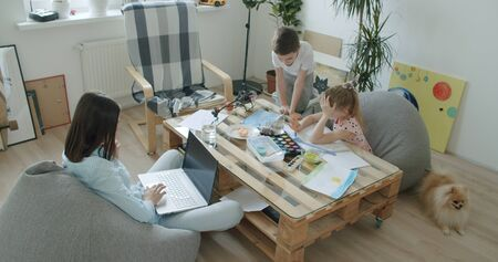 Happy mom and cute kids sitting at home, mother with little children drawing and playing with toys . Young woman works from home. Self-isolation Reklamní fotografie
