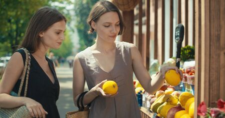 two women choosing fruits in street kiosk in tourist city center. Girls buying fruits and vegetables at farmers shop. Healthy Food