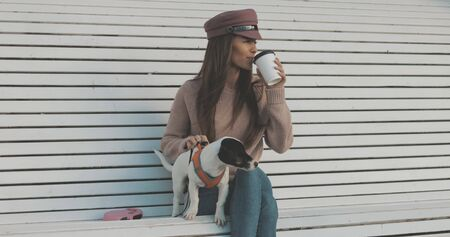 Pretty caucasian woman with dog jack russell terrier sitting on bench and drinking coffee. Cute little puppy Banco de Imagens - 147360268