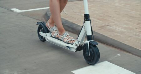 Close-up of legs of woman ride on electric kick scooter