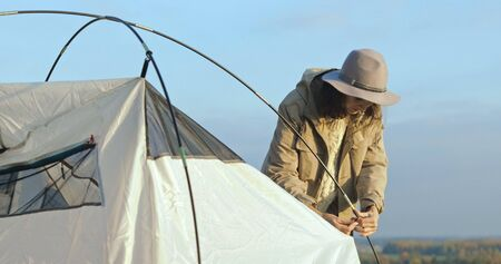 The girl sets up tent on the grass. Tourist fortifies the tent, camping. Female caucasian model on vacation