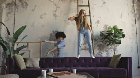 Attractive multi ethnic joyful girls dancing at modern apartment . Slow motion of group mixed race young attractive group of women eating pizza and having fun at home