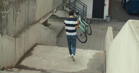 Handsome man in carrying his bicycle while going down the stairs Фото со стока
