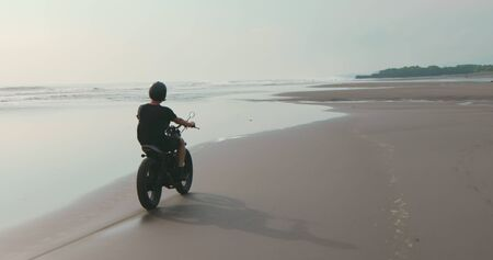 Motorcyclist driving his motorbike on ocean beach during sunset