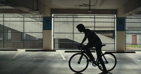 TRACKING Handsome young adult man wearing suit checking phone before riding his classic bicycle to work through an empty parking garage