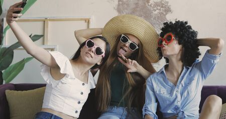 Three girls friends make selfie. Young women grimasing and posing funny at home