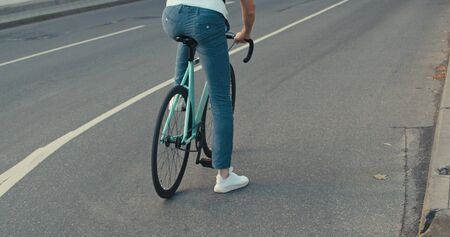 Young hipster man in casual summer cloths riding his fixed gear bike along the bike lane on city street. Shot young guy biking bicycle on road Stock Photo