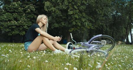Young modern woman riding bicycle in city. Girl texting reading messages on smartphone