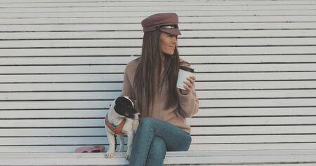Pretty caucasian woman with dog jack russell terrier sitting on bench and drinking coffee. Cute little puppy
