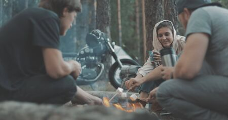 Group of happy friends around burning camping bonfire in woods roasting marshmallows talking and smiling. Hikers sitting around camp fire. Outdoor picnic in forest. Banque d'images