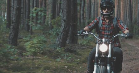 Young rider driving vintage classic custom motorcycle on forest road. Tourist with backpack on back goes to rest in camp Фото со стока