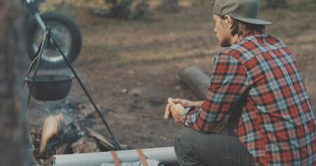 Hiker friends sitting around camp fire. Outdoor camping picnic in forest. Freedom lifestyle scene. Young couple in love sit by fireplace and talk Banque d'images