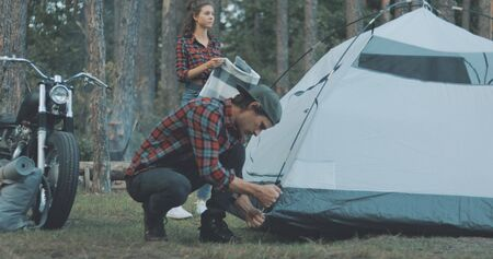 Hiker camping in forest. Guy biker sets up tent in woods. Handsome young man tourist puts hiking backpack. Countryside lifestyle scene. Banque d'images
