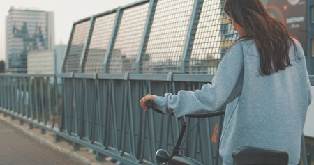 Young woman walking on city streets with bicycle , Urban biking, teenage girl and bike in town, sunset sunshine
