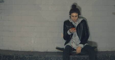 Young skater happy teen girl using a smart phone. Young caucasian woman sitting on skateboard listening to music on smartphone late at night in dark underground tunnel