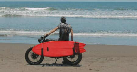 Handsome man biker surfer driving his black motorbike cafe racer with red surfboard shortboard on the beach along the ocean at sunny day