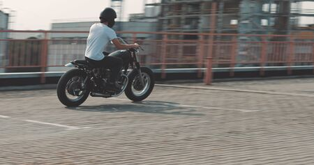 Motorcyclist drives on a motorcycle on the road in the city. Biker rides a vintage custom motorbike from 1970s . Urban lifestyle scene