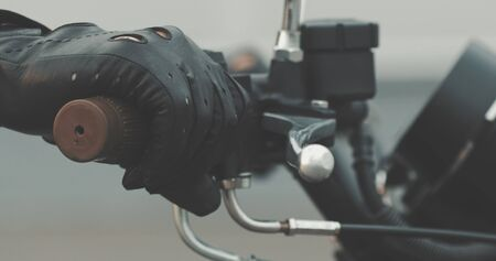 Motorbike handle grips. Close up of hand of motorcyclist holds the trottle and pushes the brake lever.