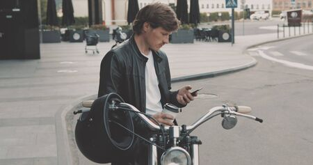 Young caucasian man biker drinking coffee usin smartphone while standing near the classic vintage motorcycle from 1970s on the street and looking away. Urban lifestyle scene