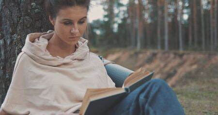 attractive young woman reading book on nature near river