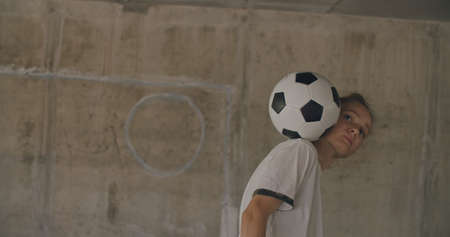 Teenager girl football soccer player doing ball tricks inside empty covered parking garage. Urban city lifestyle outdoors concepte. 4K UHD slow motion RAW graded footage
